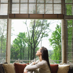 woman looks through window blinds